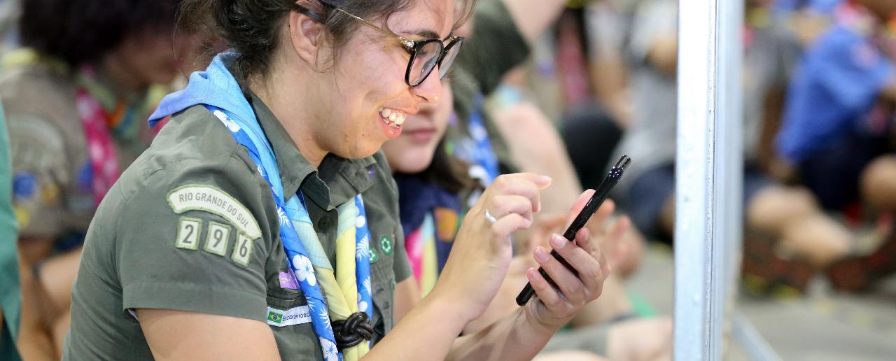 Adulto voluntário sorrindo enquanto utiliza o celular.